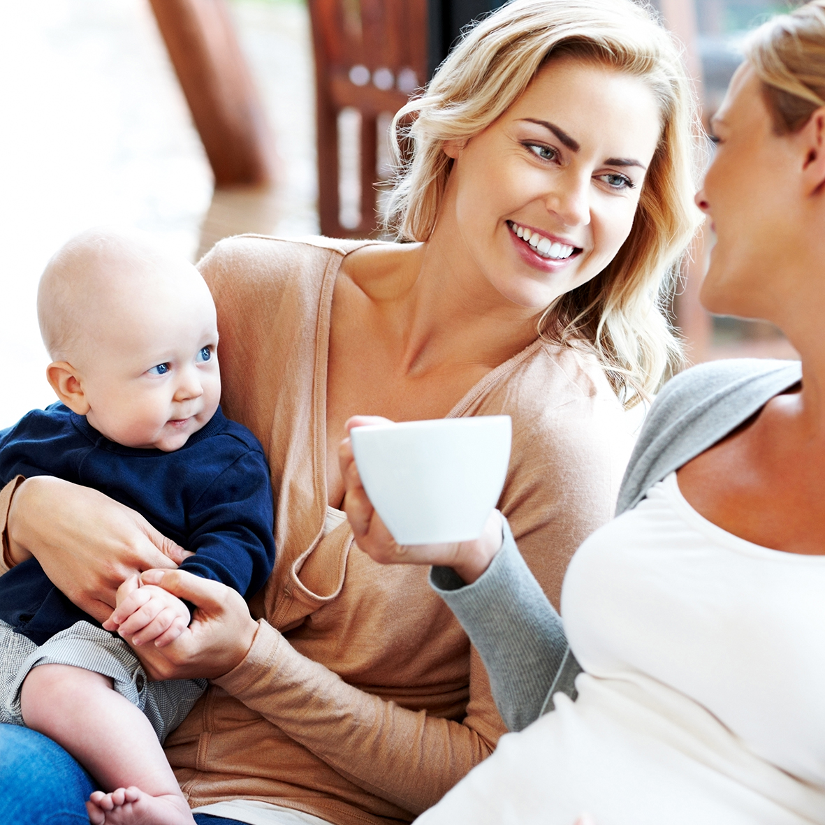 Happy pregnant woman with her friends relaxing at home