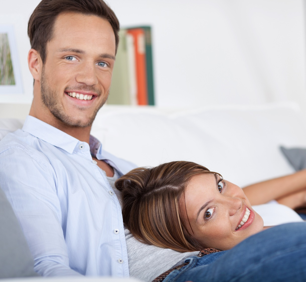 21162453 – smiling couple relaxing on couch in living room